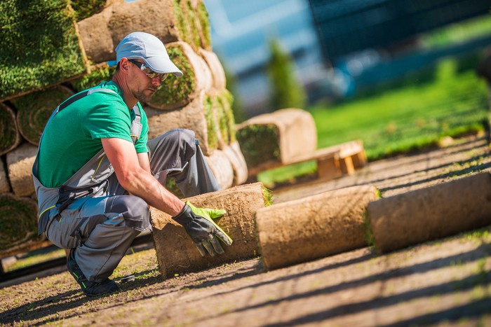 A commercial landscaping company employee installs turf in front of an office building.