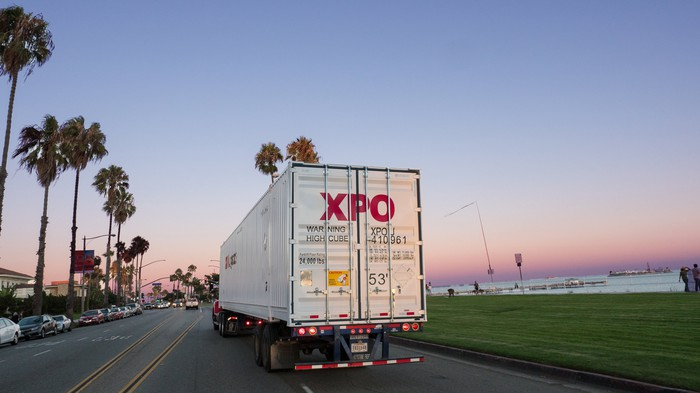 An XPO-branded truck heads down a palm tree lined highway.