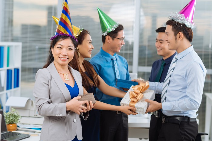 Five professionally dressed adults in party hats smiling; two are exchanging wrapped boxes