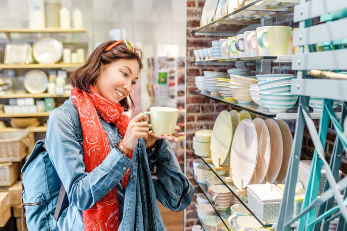 Woman holding a cup while shopping for kitchen supplies.