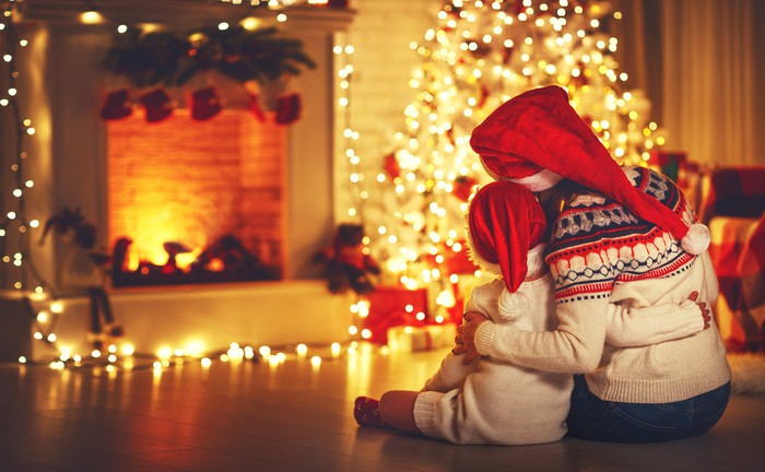 Woman and child in Santa hats sitting on floor, embracing near lit-up tree