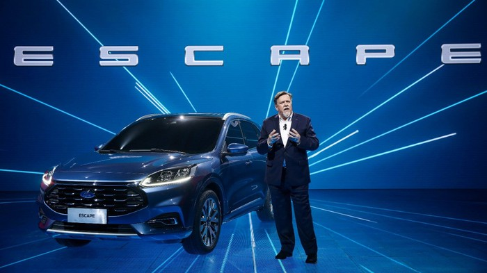 A man standing next to a blue Ford Escape SUV on a blue stage.