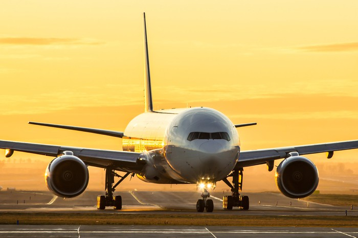 An airplane taxiing on a runway at sunrise.