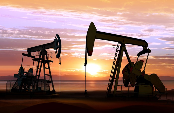 Two pumpjacks operating in a field at sunrise.