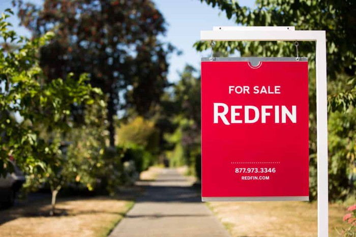 A red Redfin For Sale sign hanging in front of a property.