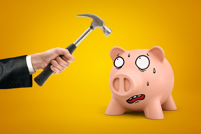 A piggy bank cowers in fear before a hand holding a hammer.