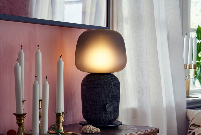 The SYMFOSONIK speaker lamp on a small table with several unlit candles.
