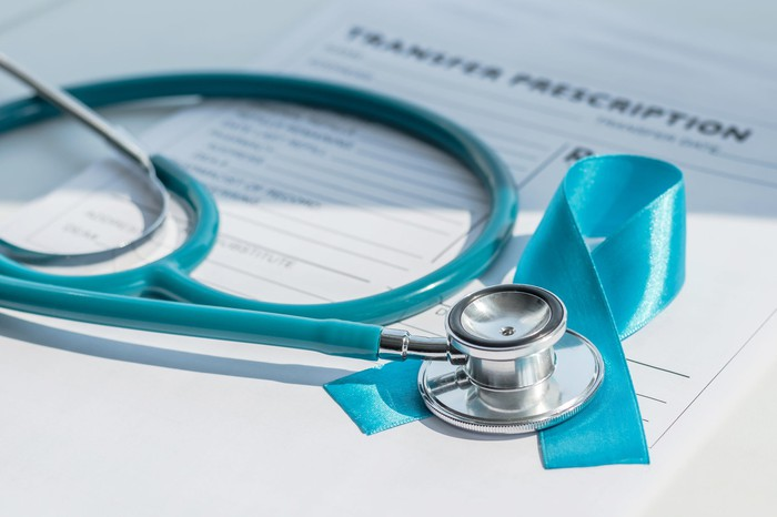 A stethoscope and a blue prostate cancer ribbon set on top of a prescription form.