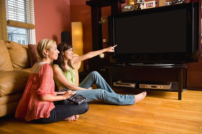 Two women point at a big screen TV.