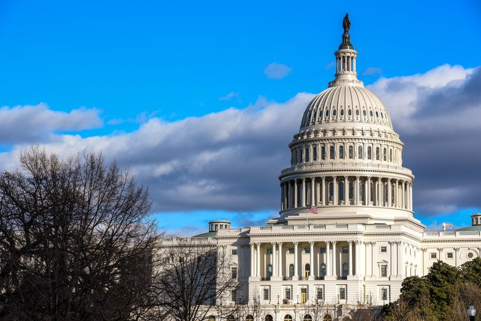 The U.S. Capitol dome under blue skies and puffy clouds.