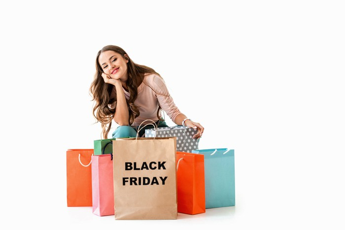 Woman sitting with shopping bags labeled Black Friday