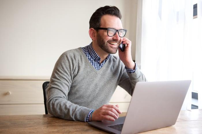 Smiling man at laptop talking on phone