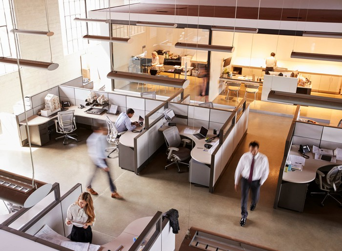An open office space with employees milling about.