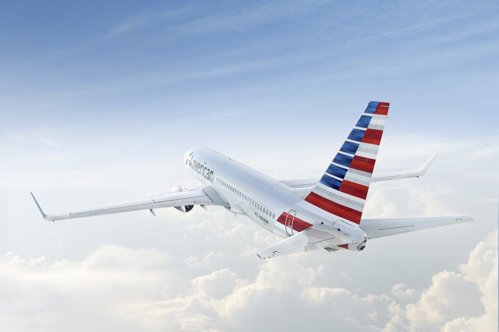 An American Airlines jet flies over the clouds.