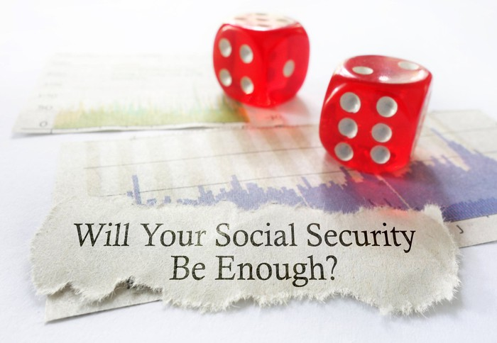 Two red dice are near a torn piece of paper on which is printed the question will your Social Security be enough?