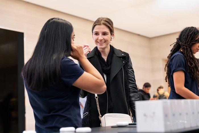 A woman trying on Apple's new AirPods Pro in an Apple store.