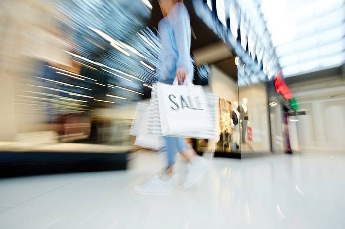 A blurred image reveals a woman holding shopping bags as she walks through a store.