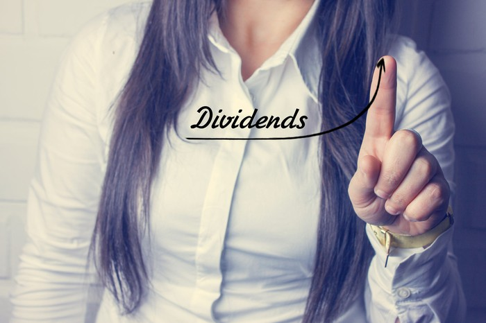 "A woman pointing at the word ""dividends"" written on a piece of glass in front of her"