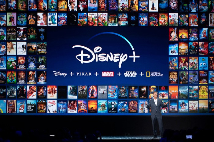 Kevin Mayer onstage presenting Disney+ with a slide featuring dozens of film and series digital poster art