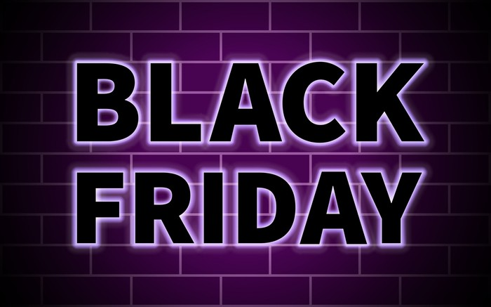 The words Black Friday in purple neon against a brick wall.
