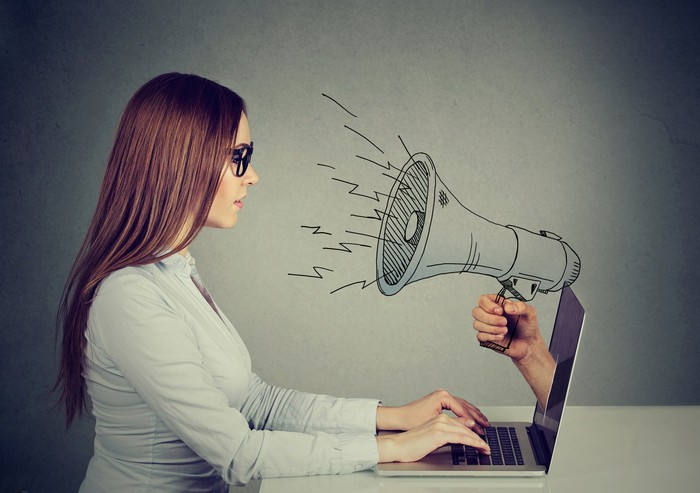 A woman types at a laptop as a hand holding a megaphone emerges from the screen.