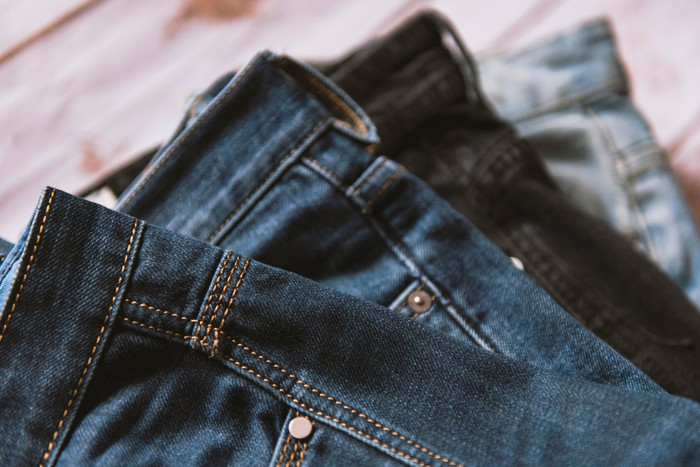Close up of several pairs of dark jeans.