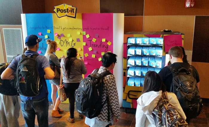 Young people putting Post-It Notes on a rainbow-colored board.
