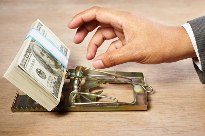 A businessman's hand reaching for a neat stack of one hundred dollar bills in a mouse trap.