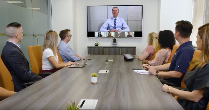 An enterprise video-conferencing call with one person broadcasting to employees seated in a conference room..
