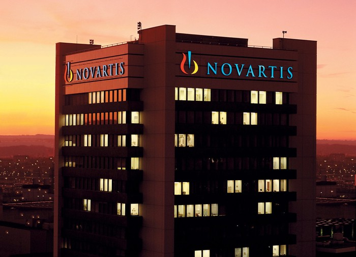 Top of office building with Novartis logo, near sunrise.