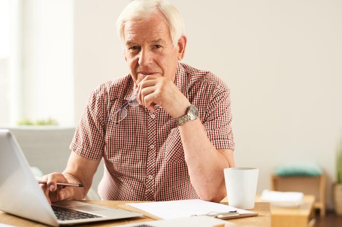 Older man holding pen while sitting at laptop