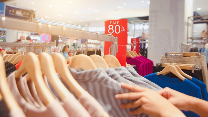 Woman reaching for blazer on rack while a sale sign hangs in the background