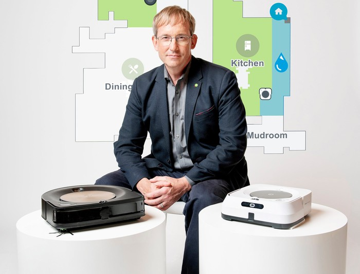 iRobot chairman, co-founder, and CEO Colin Angle sitting next to high-end Roomba and Braava robots with a house map in the background.