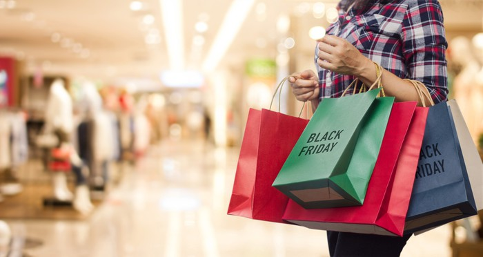 "Woman in a mall holding shopping bags labeled ""Black Friday"""