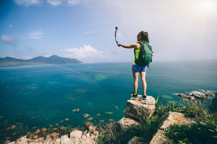 Woman holding an action camera takes a selfie while overlooking an ocean