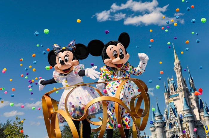 Mickey and Minnie celebrating during a Disney parade.