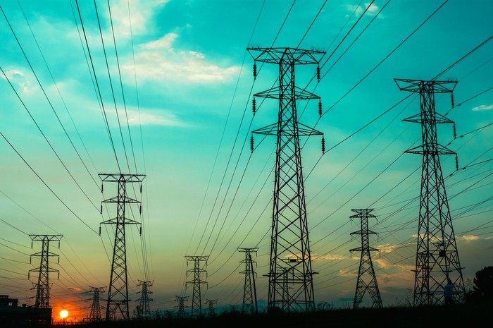electric writes and wire towers with a sunset in the background