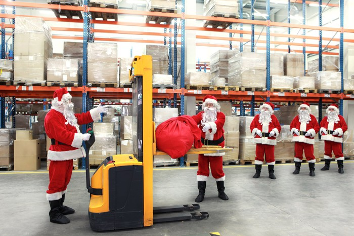 Several people dressed as Santa Claus process packages in a warehouse.