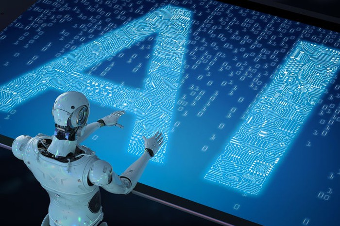 "A humanoid robot standing in front of a very large digital/circuit board with the letters ""AI"" on it."