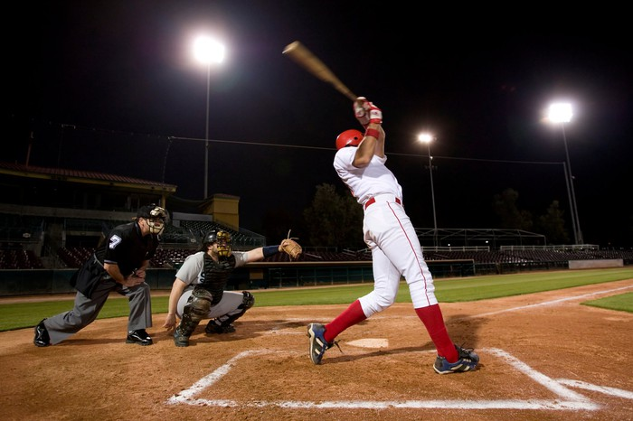 A baseball player swings at a pitch while the catcher and umpire look on.