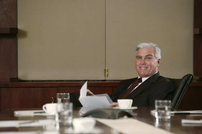 A businessman smiling from behind his desk
