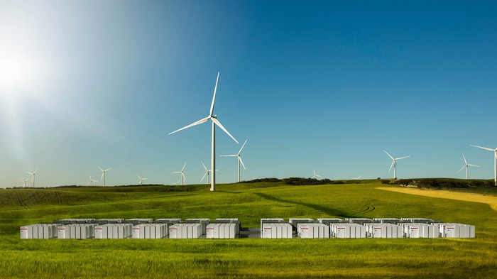 Tesla Big Battery electricity warehouse in a field in foreground and windmills in the background