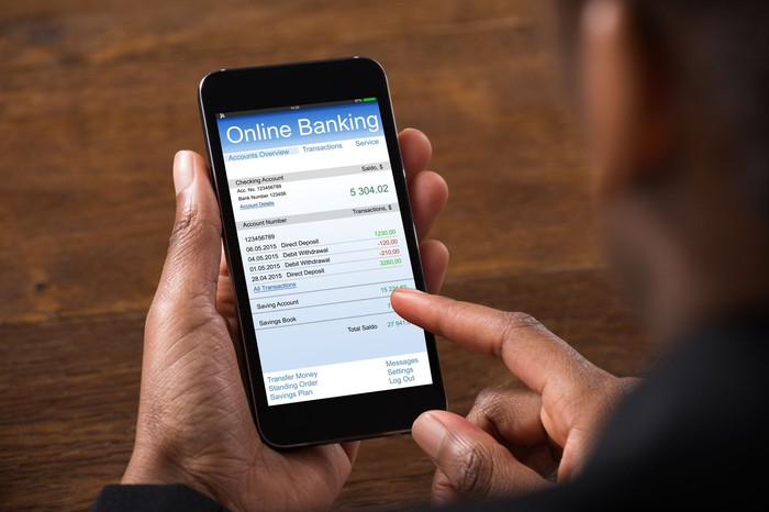 Woman using cell phone to check bank account balance.
