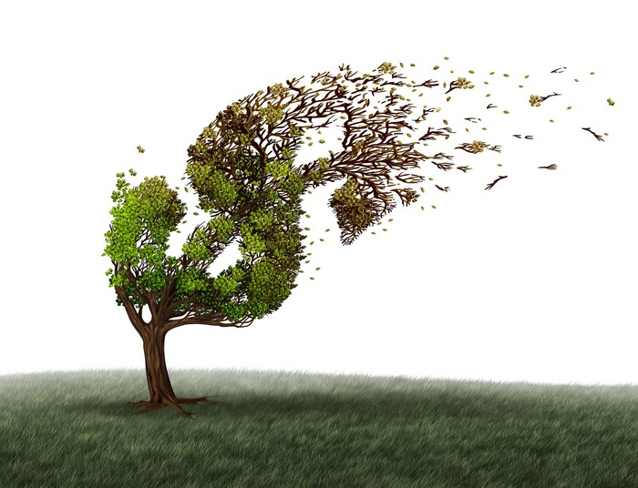 Illustration of a tree trimmed in the shape of a dollar sign, bending in heavy wind.