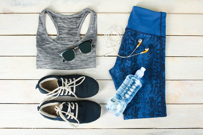 A sports bra, sunglasses, sneakers, water bottle, earphones, and capris pants laid out on a table.