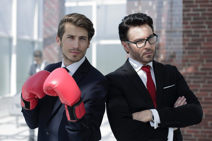 Two young businessmen stand back to back in an alley, one wearing red boxing gloves.