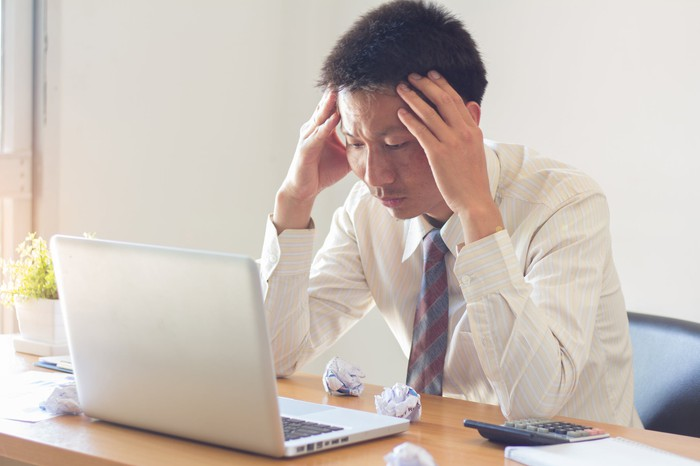 Man sitting at laptop, holding his head as if tired