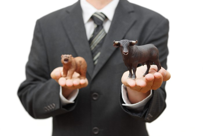 Man in suit extending a bull figurine with a bear figurine in the other hand