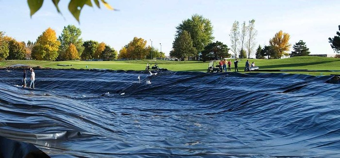 Large black plastic liner on a drained golf course pond.