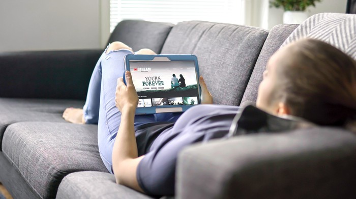 A woman laying on a couch watching streaming TV on a tablet